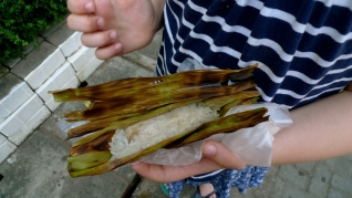 Sticky rice wrapped around a banana, grilled in a banana leaf.